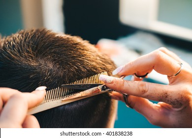 Brunette man getting a haircut by a professional hairdresser using comb and grooming scissors. Closeup view with shallow depth of field.