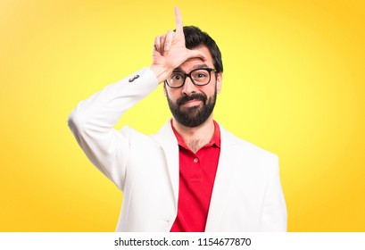 Brunette man with glasses making loser sign on colorful background