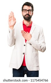 Brunette man with glasses making an oath on white background