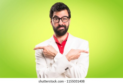 Brunette man with glasses pointing to the laterals having doubts on colorful background