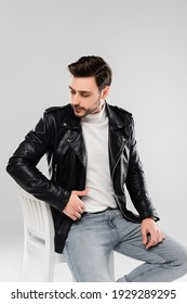 Brunette man in leather jacket sitting on chair isolated on grey