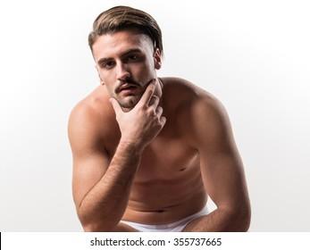 Brunette man in underwear sitting on wooden chair