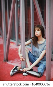 Brunette with a metal prosthetic leg posing against the background of a red carpet and grey tubes.