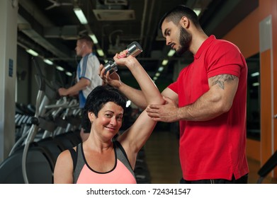 Brunette middle aged woman working out with personal coach in modern gym. Young male trainer assisting his female client while she doing triceps exercise. Healthy lifestyle, fitness and sports concept