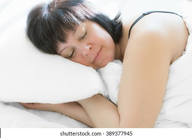 Brunette middle-aged woman lying in bed the morning