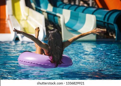 brunette model in black bikini on the inflatable ring in the swimming pool. Summer Vacation. Enjoying suntan. Weekend on luxury resort