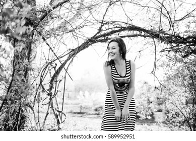 Brunette model girl at dress with stripes laughs near arch from tree. Black and white photo.
