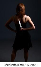 A brunette model with large knife behind her back
