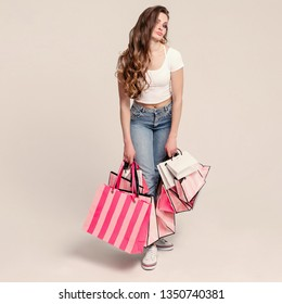Brunette model posing at camera with purchases from stores.