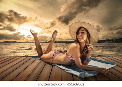 brunette model relaxing on a pier sunset