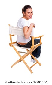 Brunette model sat in a directors chair looking back over her shoulder, isolated on white. Add your own text to the back of the chair.