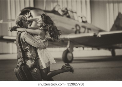 A brunette model in vintage clothing with a pilot and a WW II aircraft