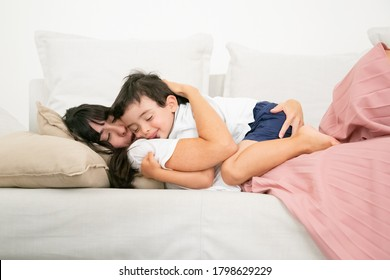 Brunette mother sleeping on couch and embracing cute son. Lovely little boy hugging young pretty mom, dreaming on sofa and smiling. Family, love and happiness concept