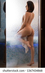 Brunette in the nude in sauna rearview