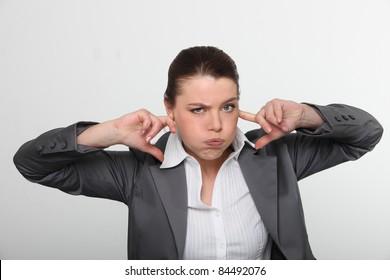 Brunette office worker with fingers in ears