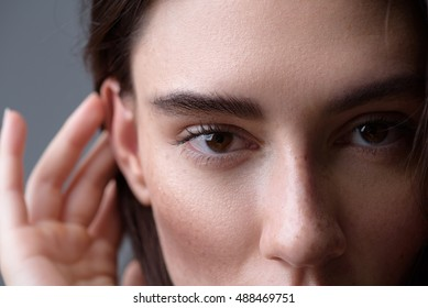 brunette on light grey background looking into camera