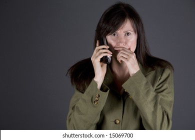 brunette on the phone wearing a green jacket