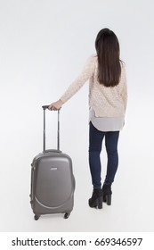 Brunette on white background looking up view from behind. Young woman in jeans with suitcase in hands. Full-length photo
