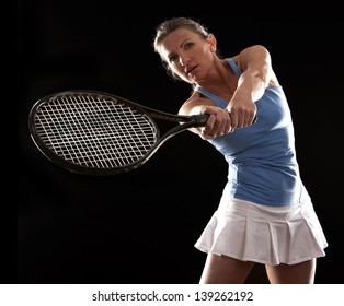 brunette playing tennis on black background
