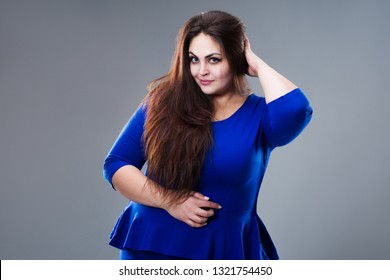 Brunette plus size fashion model in blue dress, fat woman with long hair on gray background, studio shot