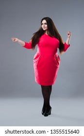 Brunette plus size fashion model in red dress, fat woman with long hair on gray background, body positive concept, full length portrait
