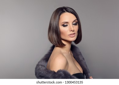 Brunette portrait in mink fur coat. Young beautiful stylish woman With Brown Short Hair isolated on gray studio background. Haircut.