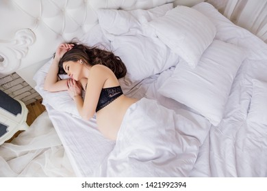 Brunette pregnant woman with big tummy sleeping in her bed