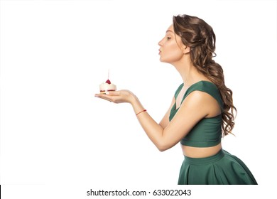 Brunette pretty beautiful caucasian woman in green festive dress blowing candle on a birthday party cupcake. Isolated white background