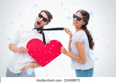 Brunette pulling her boyfriend by the tie holding heart against snow falling