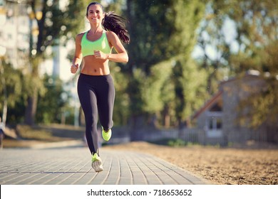 A brunette runner woman runs in the park jogging.