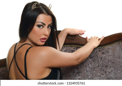 brunette sexy woman in black dress on sofa on white background