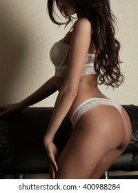 Brunette sexy woman posing in white lingerie. Young sexy lady wearing white underwear, amazing body. Slim body.