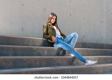 brunette and sexy woman with torn pants waiting on some stairs