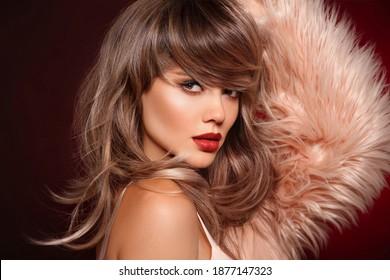 Brunette kurze Frisur. Rote Lippen machen sich aus. Schöne Frau in Pelzmantel. Herrliches Modell mit kurzen glänzenden Haaren. Konzept Farbhaar. Schönheitssalon.