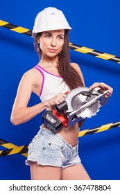 Brunette in shorts with an electric jigsaw on a blue background with a white ribbon in the protective construction helmet.
