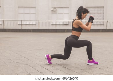 Brunette slim adult sexy fit sporty caucasian woman in sportswear on a european city streets in morning do exercises (workout) - forward lunges. Copy space