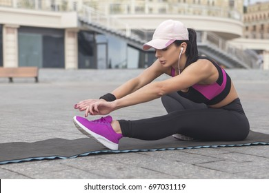 Brunette slim adult sexy fit sporty caucasian woman in sportswear on a european city streets in morning do exercises (workout), stretch her legs and butt. Copy space