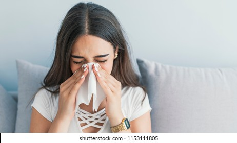 Brunette sneezing in a tissue. Sick desperate woman has flu. Rhinitis, cold, sickness, allergy concept. Pretty sick woman has runnning nose, rubs nose with handkerchief. Sneezing female.