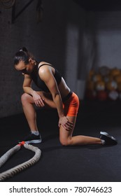 brunette sportswoman standing on knee at gym after battle rope workout and looking down. Attractive female athlete taking rest after fitness training at gym