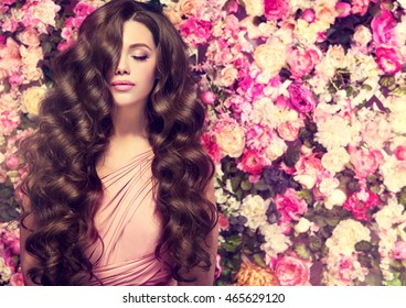 Brunette spring girl with long  and   shiny wavy hair .  Beautiful  model woman with curly hairstyle ,   background  wall of flowers .