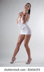 Brunette standing in a white dress