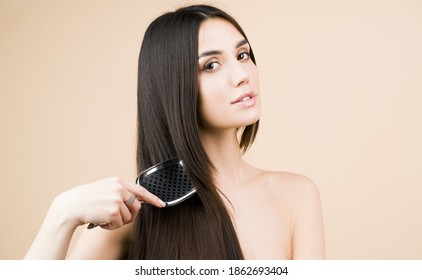 Brunette straight hair. Perfect woman with with a comb? Beautiful woman with long and shiny hair. Care. Female model after hair procedure. Natural health glance hair on beige background