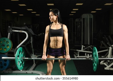 Brunette strong fitness sexy woman doing barbell squats in a gym