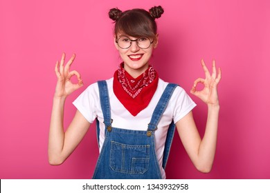 Brunette student with banches smiles, makes okay sign with both hands, shows approval. Young girl wears white t shirt, denim overalls with red bandana on neck. Body language and people concept.