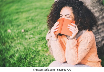 Brunette student girl with curly hair covering her face with her diary looking embarrassed sitting against a tree on a grass of park - Young woman writing on her copybook laughing outdoor