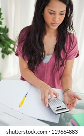 Brunette student taking a calculator to do her homework