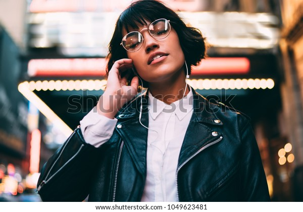 Brunette stylish hipster girl with close eyes enjoying listening electronic music in earphones feeling carefree on free time standing in night city downtown of New York with neon illumination lights