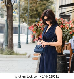 Brunette in sunglasses with handbag on a sunny summer day outside in the city. Active style of the business woman and classical style in clothes.