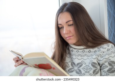 brunette in sweater sitting on the window sill and reading book