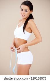 Brunette sweety measuring her waist  she standing over beige background